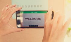 """Hands hold a smartphone in front of a sign saying """"Bienvenue"""" and the smartphone reads """"Welcome"""" #SmartphoneInHand"""