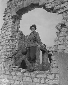 WAC Emma Dale Love, wearing a WAC field jacket and holding her helmet, poses among ruins in France, October 1944 ~