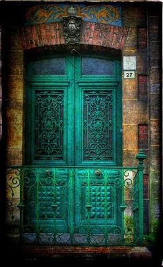 Green double doors with scrolled wrought iron work...#27  door knobs in the middle of the doors :)