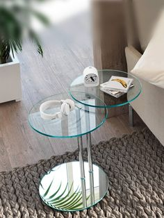 This glass table is a great bedside or sofa side table. This glass table is made up from two circular glass table tops joined by discrete metal columns to and glass base. The metal column design allows for 360 degree rotation of one of the tops- a really handy feature when extra space is required.