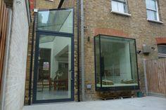 Large pivot door, glass roof and oriel bay window.