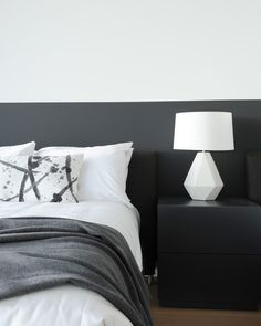 A black and white in a guest bedroom is a timeless and classic way to create drama. This white lamp with white bedding ties in with the custom black headboard