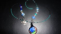 This is a Large Glass Beaded Book thong/Marker. It has a beautiful Murano Glass Pendant in the style of a blue rose on black background and some sparkle dust in the background. There is also an elephant on the other end with a groupf of matching beads of different materials, crystals, stone, Handmad...