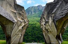 A view through the two halves of the monument to the Partisan Brigades who fought in the Battle of Sutjetska during World War 2, showing the mountains beyond.