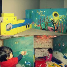 Submarine & Under the Sea Cardboard Playhouse for my twins. Refrigerator sized box for the house and 2 Carseat boxes for the submarine. Inside are LED christmas lights on the roof, blankets, toys and photos of sea animals on the walls.