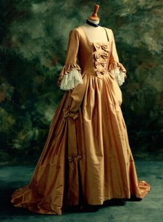 An eighteenth century style wedding dress shown in a pink/ gold silk dupion with ivory  lace sleeve flounces. The boned bodice has back lacing. Accurately made to customer's measurements
