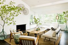 A bright, open mid-century modern living room with house trees, mid-century loungers and mid-century chairs! // 13 Mid-Century Modern Living Rooms for Inspiration - Some affordable, some luxury living rooms, but all in a beautiful style with mid-century furniture, mid-century decoration, and great taste! If you're looking for ideas, click here to find some!