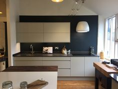 Pure handless cabinetry from John Lewis of Hungerford. Earl Grey cabinets with a Neolith ceramic worktop - a beautiful pairing.
