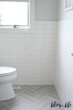 Full bathroom remodel with gray herringbone floor tile, white subway tile walls,. Full bathroom remodel with gray herringbone floor tile, white subway tile walls, black vanity and p Grey Bathroom Floor, Light Grey Bathrooms, White Subway Tile Bathroom, Bathroom Flooring, Subway Tile Bathrooms, White Tiles Grey Grout, Flooring Tiles, Dream Bathrooms, Bathroom With Tile Walls