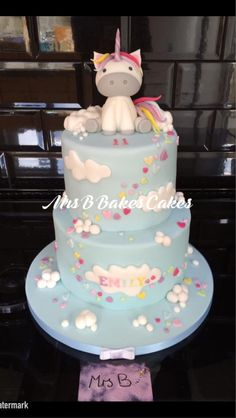 Unicorn Rainbow Showers. 2 tiers of cake in sky blue with tiny heart shaped rain fall and clouds. Entirely handcrafted, entirely edible including sugarpaste fondant Unicorn https://www.facebook.com/mrsbcakeologist/
