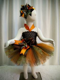 Darling little Camo Tutu that has camo print tulle along with dark brown and orange tulle tied onto orange ribbon that ties into a big bow in the