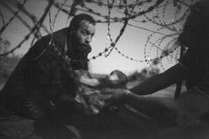フェンス越しに赤ちゃんを渡す男性。2015年8月28日セルビアとの国境に接するハンガリーのルスケ(Röszke)村で撮影。