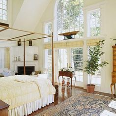 """A master bedroom addition    To take advantage of the wooded view from their home, the couple that built this master bedroom addition built a """"wall"""" of glass with a Palladian window above, French doors, and sidelights overlooking their property. Note the secondary role assigned to the understated fireplace."""