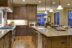 #Kitchen of the Day: A lovely kitchen with rich chocolate stained cabinets, hardwood floors, and a large island. See it from another angle: Traditional Dark Walnut Kitchen Cabinets #9 (Kitchen-Design-Ideas.org)