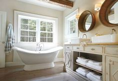 French bathroom features silver arched mirrors over marble bowl sinks accented with vintage style faucets on gray double vanity with cabriolet legs atop wood floors.