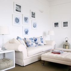 Shell and coastal inspired pictures and prints are grouped together above the white sofa in this living room to add pretty coastal touches.