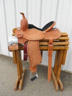 "Custom Bar H Barrel Racer | Bar H EquineThis beautiful Custom Barrel Saddle was hand made right here in the great USA. Rawhide covered tree, Full Quarter Horse Bars, 4"" Cantle Height. This medium oil finish is 1/2 tooled with diamond waffle tooling and a boomerang border is a perfect match to many of our Bar H tack sets. Matching Hoof Pick Holder, Stainless steal hardware and warranty included. Seat Size: 14 Inches"