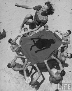 Teenaged Boys Using Blanket To Toss Their Friend, Norma Baker, Into The Air On The Beach, 1948