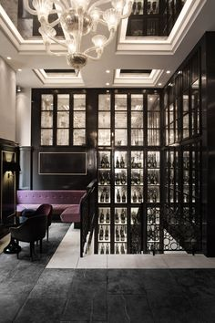 love the purple against the black...squares to showcase jewelry, perhaps between columns? Chandelier is divine and very sexy, ceiling divisions with mirrors and can light    Balthazar Champagne Bar by SPACE Copenhagen, Copenhagen hotels and restaurants