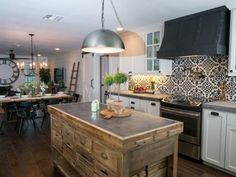 The kitchen in the second story of the Meek home features a custom island, a unique tile backsplash, new stainless steel appliances, and shiplap walls, as seen on Fixer Upper. (After #11)