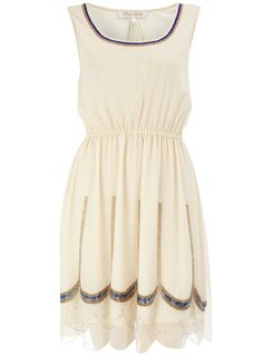 a creamed colored dress with blue and gold beaded accents