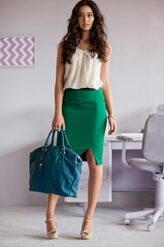 Green pencil skirt and a cream colored top with a bright blue purse.