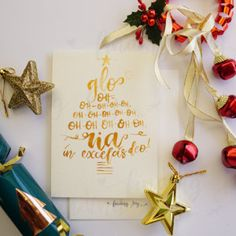 """A hand-painted Christmas card featuring phrase(and popular Christmas carol lyrics) """"Gloria in excelsis deo"""" lettered in gold ink, in the shape of a Christmas tree."""