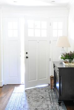 A glass paned door opens to a chic foyer boasting a bone inlay mirror over a black dresser atop a black and blue rug.
