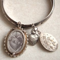 Held inside this two sided Victorian sterling silver and paste locket, is a beautiful assemblage creation of the Sacred Heart of Mary taken from an antique lace holy card.  The reverse side has an image of The Sacred Heart of Mary wrapped in a crown of roses.