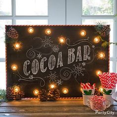DIY a light-up cocoa bar sign! All you need is a black foam board, clear globe string lights, paper straws, pine cones & a pine needle garland!