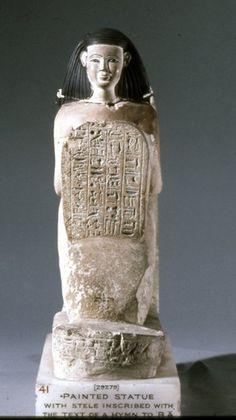 Limestone kneeling stelophorous figure; four columns of Hieroglyphic text on the stela; row of incised Hieroglyphic text on the round front of the plinth; wide back-plinth; traces of colour; head lost.