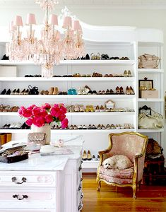 Pink chandelier, chair, and handbags to accessorize the closet.