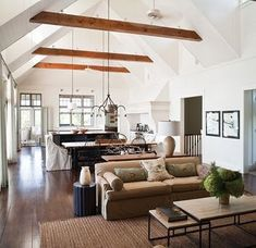 Bright and open floor plan living/dining/kitchen with high ceilings and beams