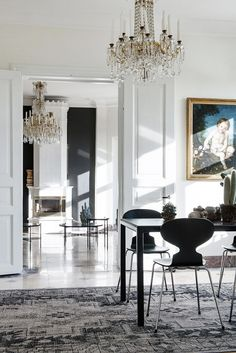 The quirky silhouette of these modern chairs are a great foil to the opulent chandelier and framed art