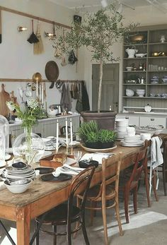 Large wooden table, eclectic styles of chairs, and country finish