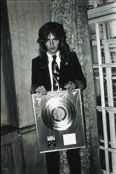 Roger Taylor with 'Queen II' award at Royal Cafè in Soho, London on September 1974. Photo by Mick Rock.
