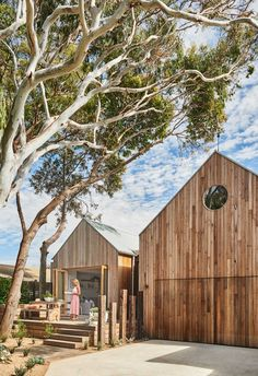 A modern beach house with a timber-clad exterior and round glass window. Timber Cladding, Timber Flooring, Australian Homes, Beach Cottages, Bungalow, Building A House, Beach House, Real Estate, Exterior