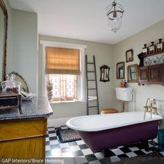 Eine lilafarbene freistehende Badewanne bringt einen Hauch Prunk ins Bad. Einen Teil dazu tragen sowohl Form und Material der Armaturen als auch klassische Elemente …