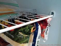 Clip opened bags underneath a shelf for a super organized freezer