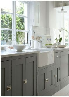 Farrow and Ball painted kitchen units, white belfast sink, white walls & floors