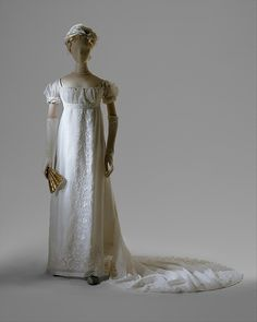 1804-1805 ca.  White Gown, French. Front View. Vertical embroidery down front of white cotton transparent mull dress with long train, short square bodice, short puffed sleeves.  Vertical white embroidery was fashionable at this time. Very sheer cotton mull probably imported from India already embroidered with heavy white cotton thread in transparent mull.  metmuseum.org                      suzilove.com
