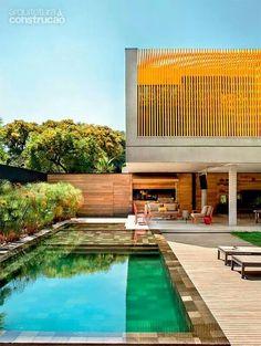casa de Vidro e concreto , com brise metalico amarelo