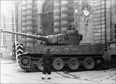 Panzerkampfwagen VI Tiger Ausf. E (Sd.Kfz. 181) Nr. 222  Des enfants jouent avec l'épave de ce Tiger de début de production (la « Rommelkist » semble même être un modèle pour Panzer III/IV). Il manque entre autre chose 4 roues de route au train de ce schwere Panzer. Plus surprenant, les chenilles semblent être celles utilisées lors des déplacements sur plateforme ferroviaire. Un impact est visible sur le mantelet du canon.   Cette photo me fait penser à une des scènes du film Der Untergang…