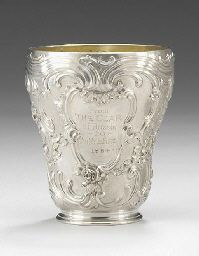 A SILVER BEAKER BY FABERGÉ, WORKMASTER JULIUS RAPPOPORT, MOSCOW, CIRCA 1896. Chased with rococo scrolls and trefoil pattern, the front cartouche with the engraved inscription 'From the Czar of Russia to Sir Myles Fenton 1894', gilt interior.