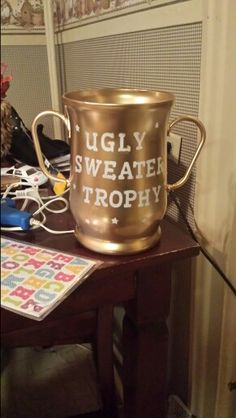 "DIY  ugly chrostmas sweater prize! I took an old glass vase , hot glued two plastic  coat hanger hooks on the side and spray painted the front white. Then I took sticky letters ($1 @ dollar general) and wrote ""ugly sweater trophy"" and spray painted the whole thing gold. Once it dried I peeled off the letters and for a total cost of $4 I made a trophy!!"