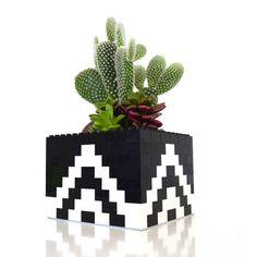 Les LEGO, c'est fun, ça rappelle l'enfance et ça apporte une petite touche de couleur à n'importe quel intérieur. Alors, direction la chambre des enfants pour leur piquer leurs jouets (chuuuut!) et pimper votre déco !    Image: Pinterest cherrywoodartfair.com    Focus : pot de fleur, cache pot, lego, noir et blanc, design, cactus