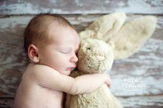 Newborn hugging stuffed animal