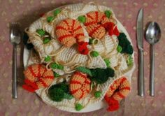 Shrimp Scampi Scarf  Ashley Gerst knitted shrimp and noodles into a scarf that looks just like a plate of scampi when it's rolled up. It looks like that around your neck, too. And it's for sale at her Etsy shop, where you'll find other knitted food.