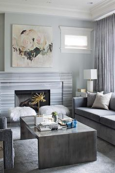 Contemporary gray living room features a pink rose canvas art placed above a gray striped marble fireplace mantle.