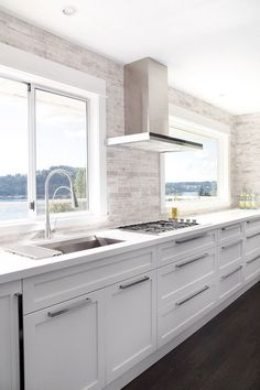 Contemporary kitchen with white cabinetry accented with nickel hardware alongside sleek white quartz countertops with a ceiling height linear mosaic backsplash.
